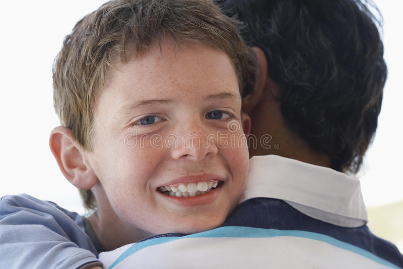 Lycklig son som omfamnar fadern royaltyfria foton