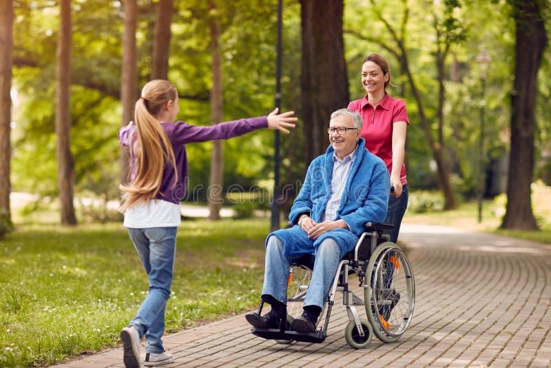 Lycklig sondotter som välkomnar henne rörelsehindrad farfar i wheelc arkivbilder