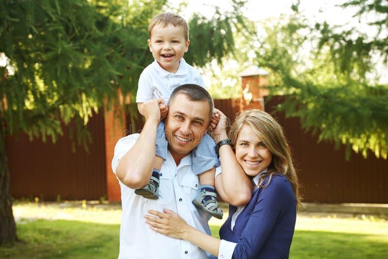 Lycklig spela familj utomhus unga föräldrar med sonen i sommar Mamma, farsa och barn arkivfoto