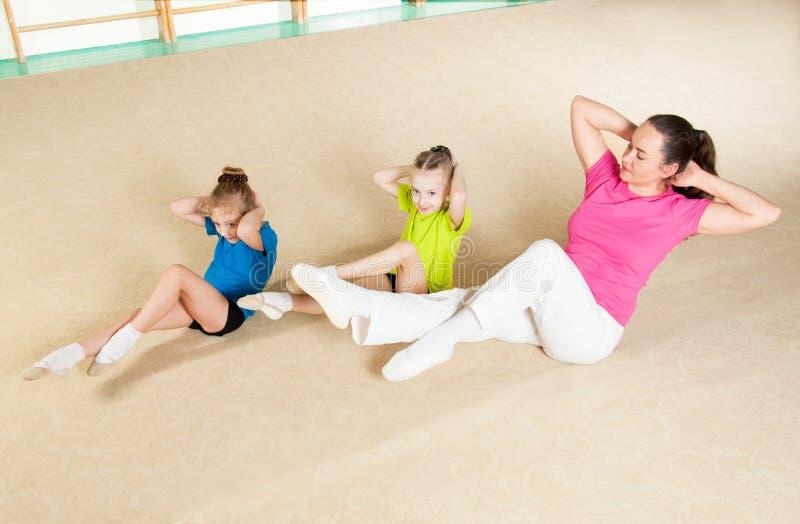 Lycklig sportig familj i idrottshall royaltyfri foto