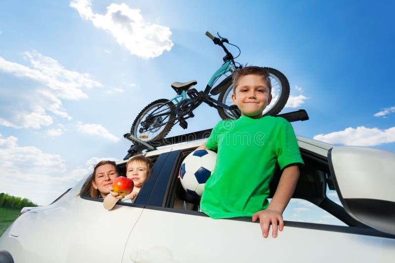 Lycklig sportig familjresande med bilen i sommar arkivbild