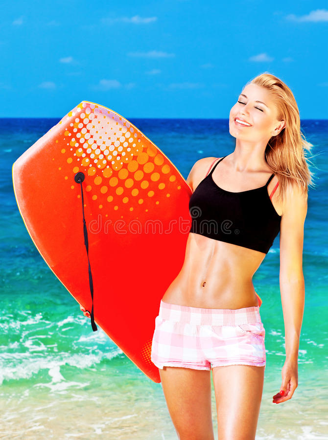 Lycklig sportig flicka som spelar kroppbrädet på stranden arkivbilder