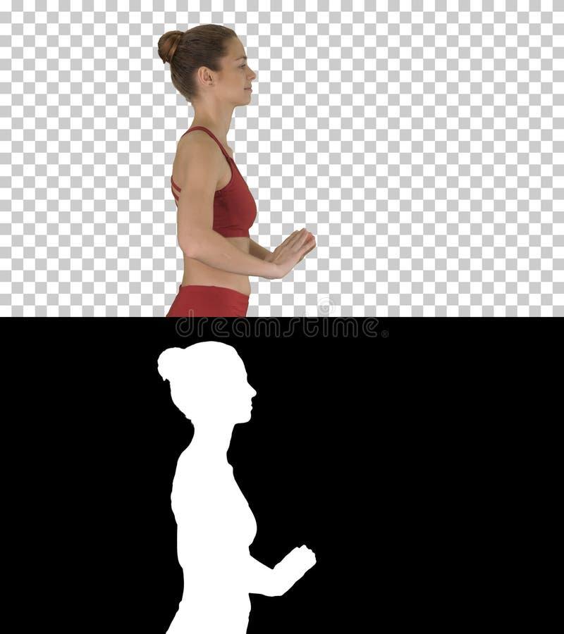 Lycklig sportig kvinna som gör yoga som andas övning, medan gå, Alpha Channel arkivfoton