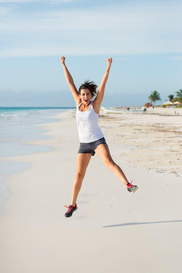 Lycklig sportig kvinnabanhoppning på den karibiska stranden fotografering för bildbyråer