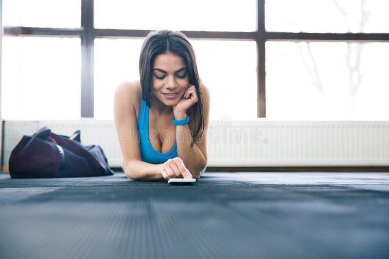 Lycklig sportkvinna som ligger på golvet med smartphonen arkivfoto