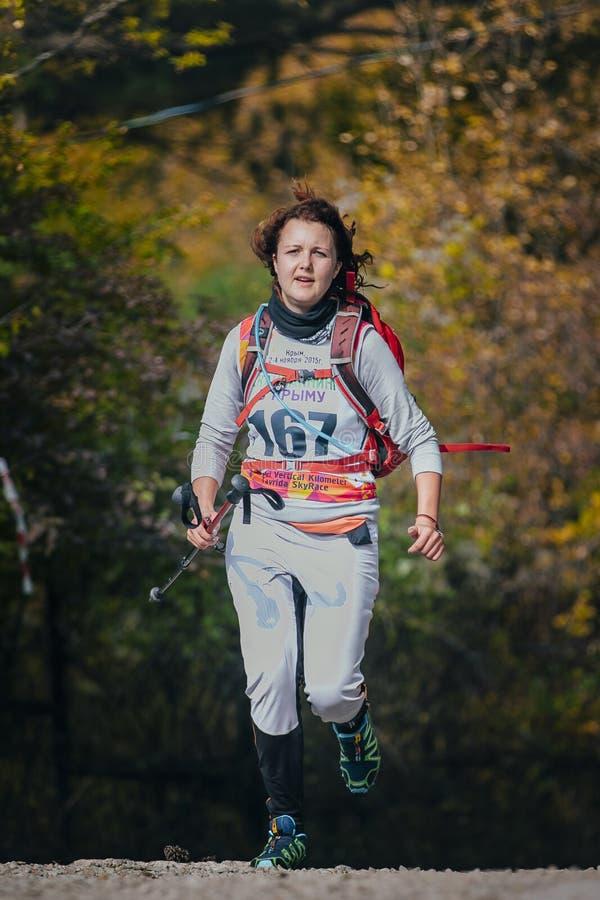 Lycklig spring för den unga kvinnan i höst parkerar med nordiska gå poler royaltyfria bilder
