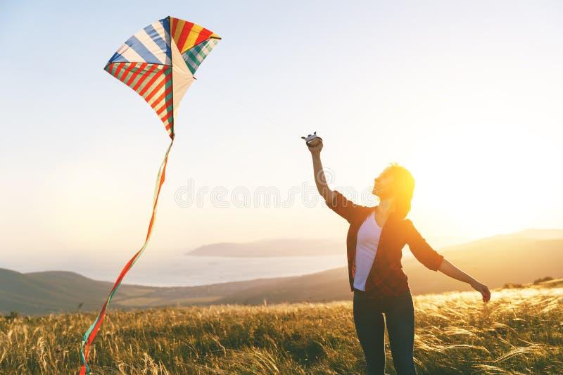 Lycklig spring för ung kvinna med draken på gläntan på solnedgången i sommar royaltyfri foto