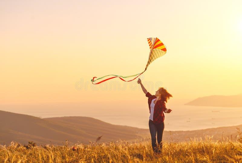 Lycklig spring för ung kvinna med draken på gläntan på solnedgången i sommar royaltyfri fotografi