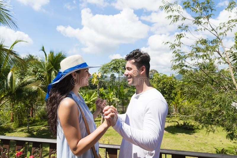 Lycklig ställning för man- och kvinnaHodling händer på sommarterrass eller unga attraktiva par för balkong över tropisk skog arkivfoton