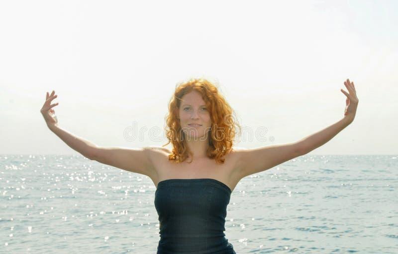 Lycklig lycklig stående av en ung elegant rödhårig lockig kvinna med utsträckta armar vid havet på stranden i Italien med kopian arkivfoto