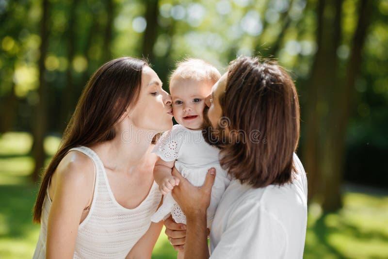 lycklig stående för familj Den unga mörker-haired fadern och hans härliga fru att kyssa deras förtjusande behandla som ett barn d arkivbilder