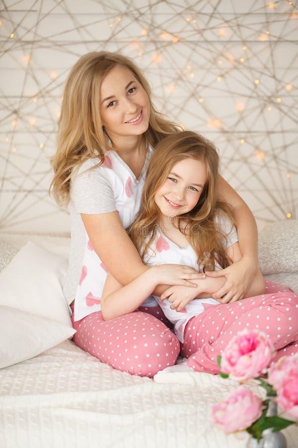 lycklig stående för familj Moder och dotter som kramar i säng och ser kameran i pyjamas modern inre loft för design royaltyfria foton