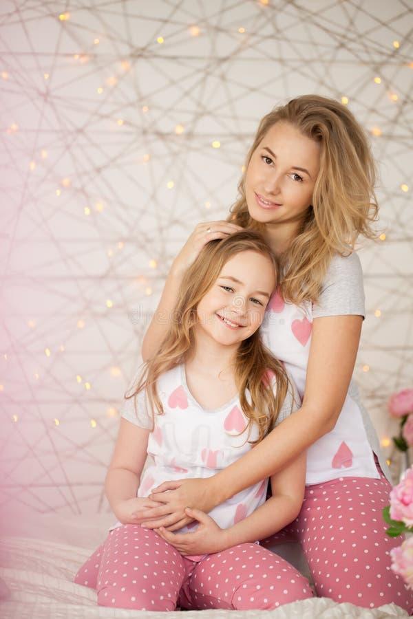 lycklig stående för familj Moder och dotter som kramar i säng och ser kameran i pyjamas modern inre loft för design arkivfoto