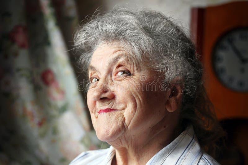 Lycklig stående för gammal kvinna på en mörk bakgrund royaltyfri foto