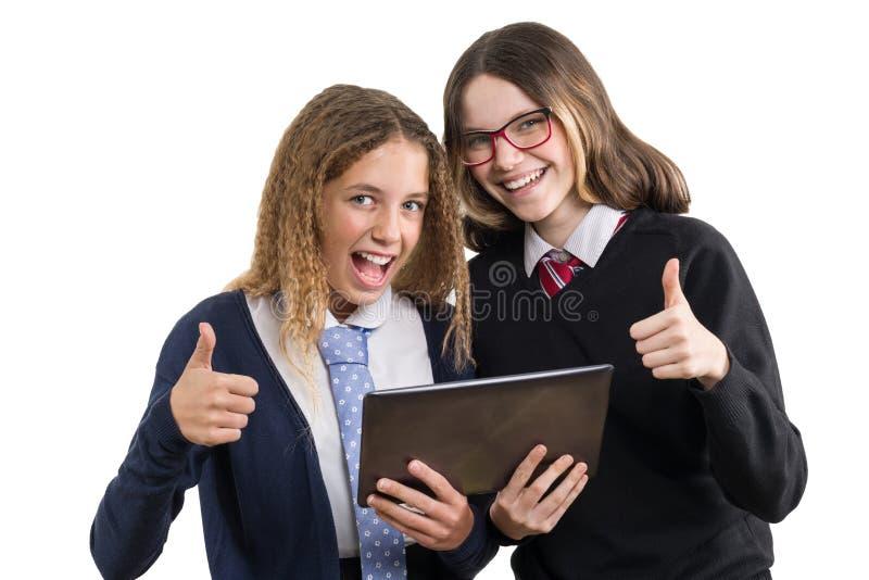 Lycklig stående för högstadiumväncloseup Tonårs- flickor i skolalikformig med minnestavlan, och visningen tummar upp, bilden är i arkivbilder