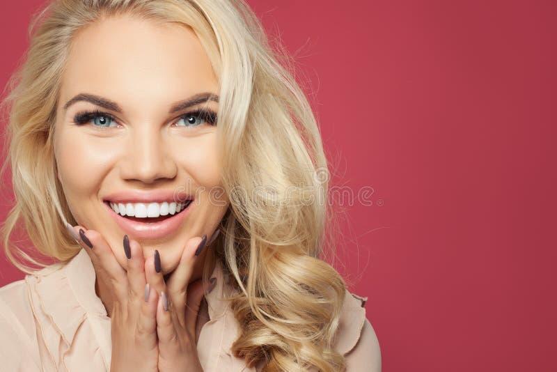Lycklig stående för kvinnaframsidacloseup Skratta flickan på rosa bakgrund, nätt framsida royaltyfri fotografi