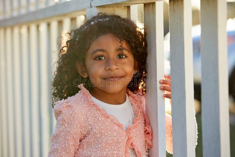 Lycklig stående för litet barnungeflicka i ett parkerastaket royaltyfria foton