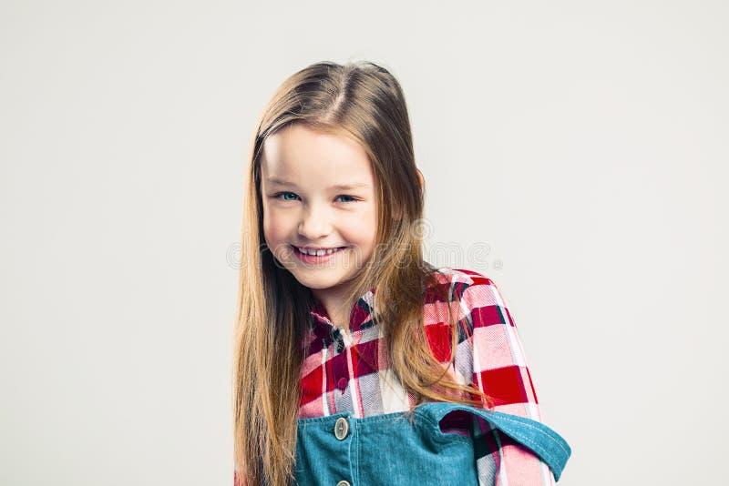 lycklig st?ende f?r barn lilla flickan ler och visar sinnesrörelse skytte för studiomodeunge royaltyfria foton