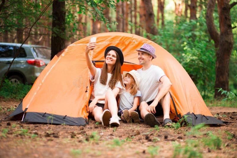 lycklig st?ende f?r familj Campa, vandring, teknologi och folkbegrepp - lycklig familj med smartphonen som tar selfie arkivfoton
