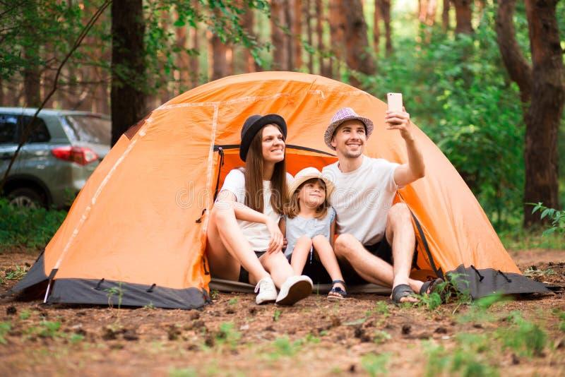 lycklig st?ende f?r familj Campa, vandring, teknologi och folkbegrepp - lycklig familj med smartphonen som tar selfie arkivbild