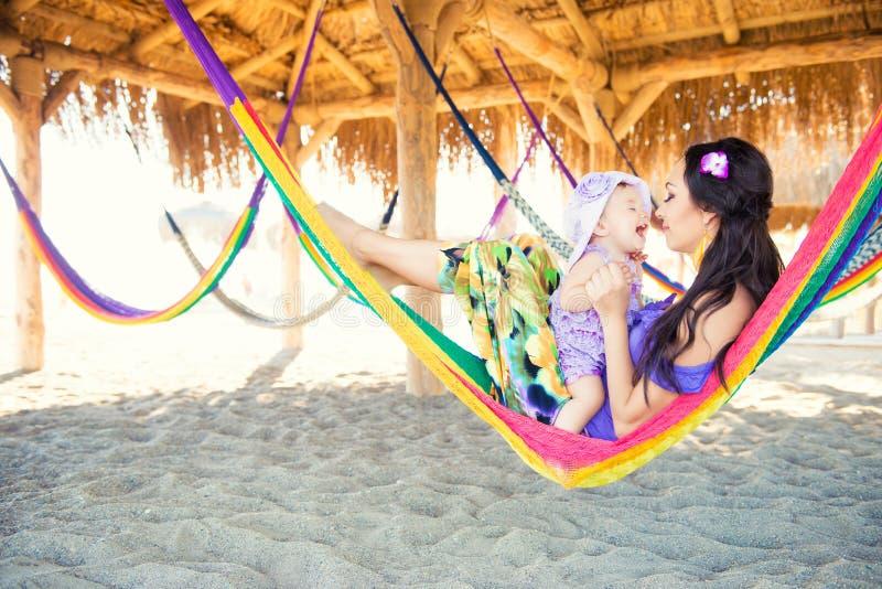 Lycklig stilfull familj med den gulliga dottern som kopplar av i hängmatta på sommarsemester i aftonsolljus på stranden arkivfoton