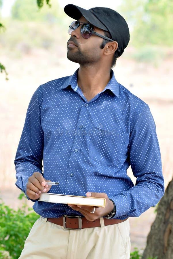 Lycklig stilfull indisk ung utomhus- affärsmanläsebok arkivfoton