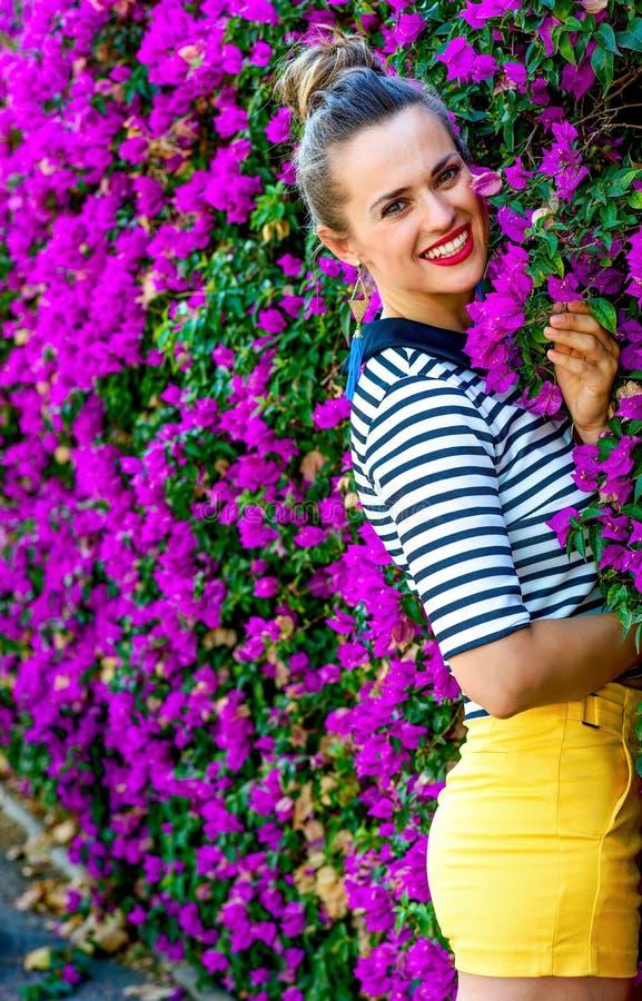 Lycklig stilfull kvinna mot färgrik magentafärgad blommasäng royaltyfria foton