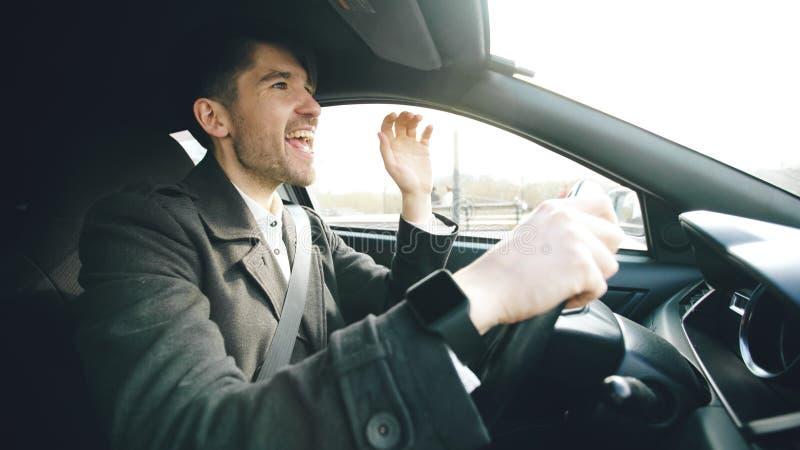 Lycklig stilig affärsman som kör bilen och att sjunga Mannen är lycklig, når han har gjort avtal och kör hem royaltyfri foto