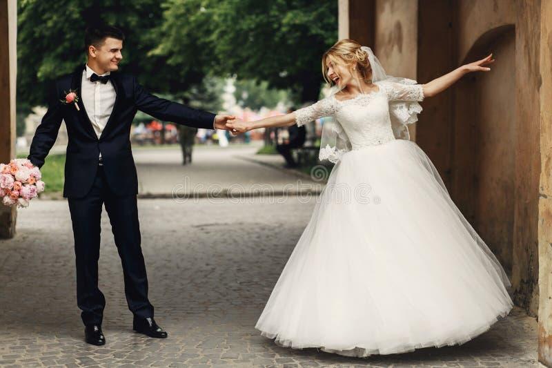 Lycklig stilig brudgum och blond härlig brud i vit klänning D arkivfoton