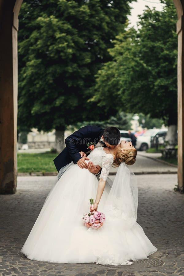 Lycklig stilig brudgum och blond härlig brud i vit klänning K royaltyfria bilder