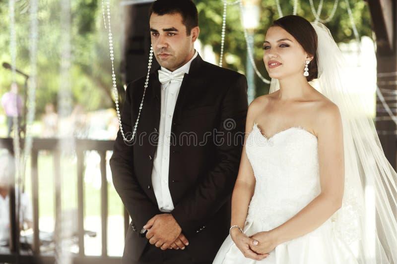 Lycklig stilig brudgum och härlig brud i den vita klänningen i weddi royaltyfria bilder
