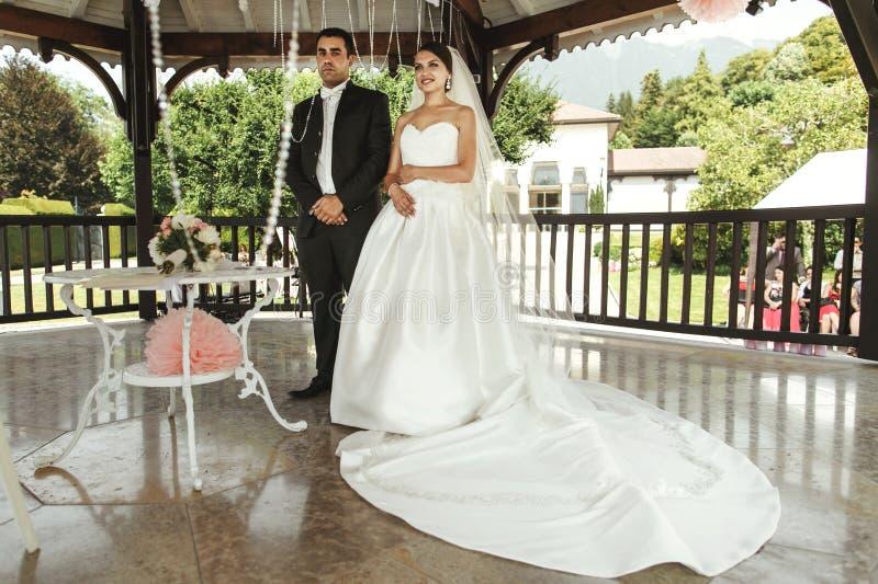 Lycklig stilig brudgum och härlig brud i den vita klänningen i weddi arkivbilder