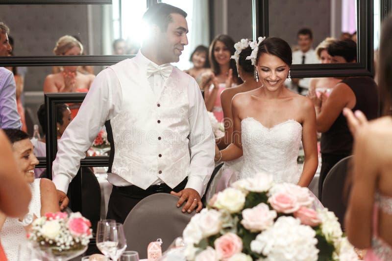 Lycklig stilig brudgum och härlig le brud med gäster på arkivfoto