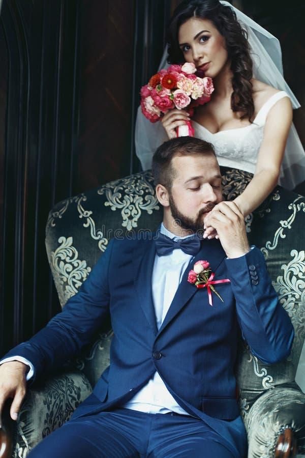 Lycklig stilig brudgum på läderstol som kysser handen av en friare royaltyfria bilder