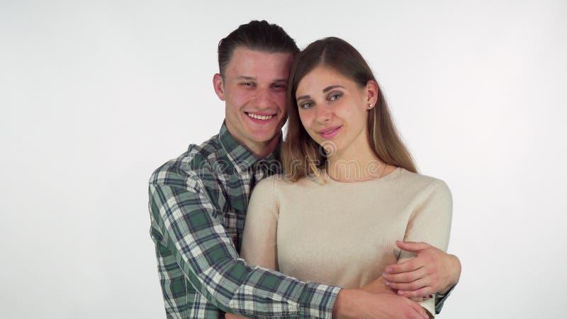 Lycklig stilig man som kramar hans härliga flickvän royaltyfri bild
