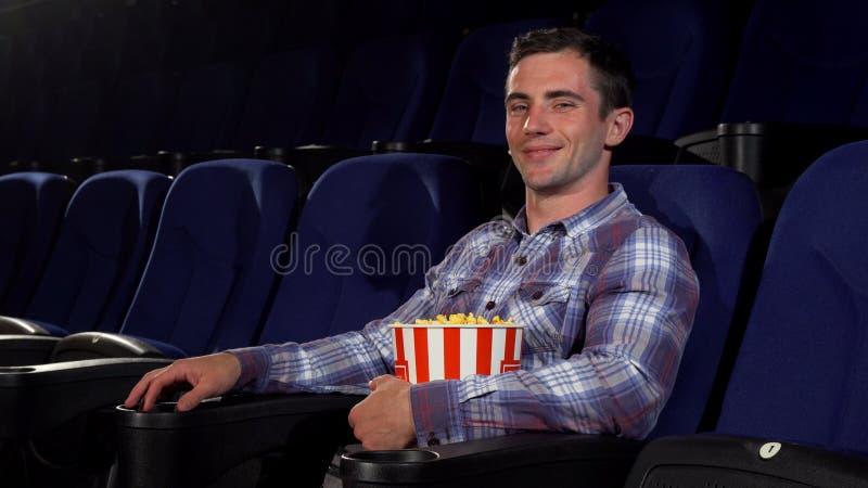 Lycklig stilig man som ler joyfully att sitta på bion arkivbild