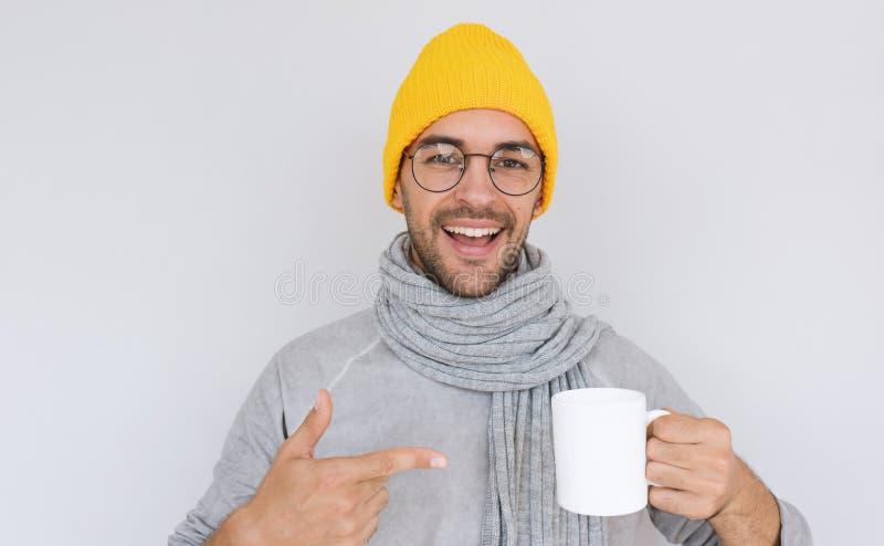 Lycklig stilig skäggig man med den vita kopp te som bär den gula hatten och den gråa tröjan med halsduken i höst eller vinter gla arkivbilder