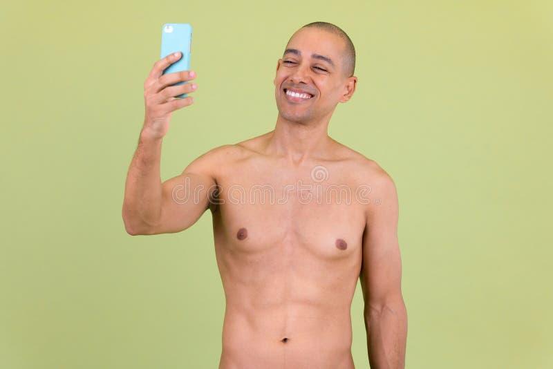 Lycklig stilig skallig mång- etnisk man som tar shirtless selfie arkivfoton