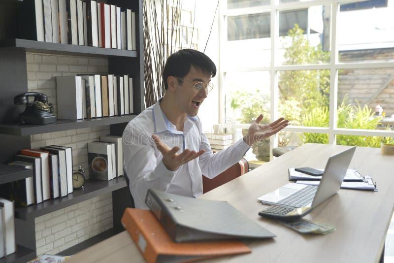 Lycklig stilig ung affärsman som arbetar på hans skrivbord arkivfoto