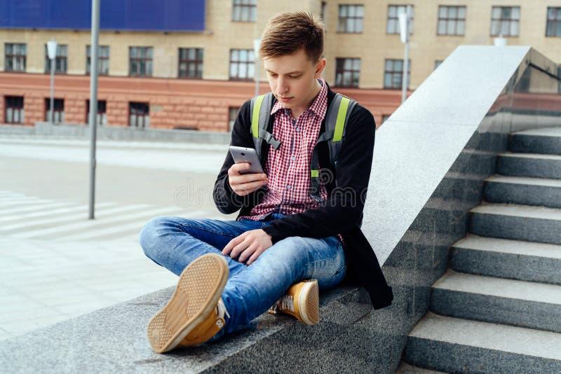 Lycklig stilig ung man med ryggsäcken som nära sitter på stenen arkivbilder
