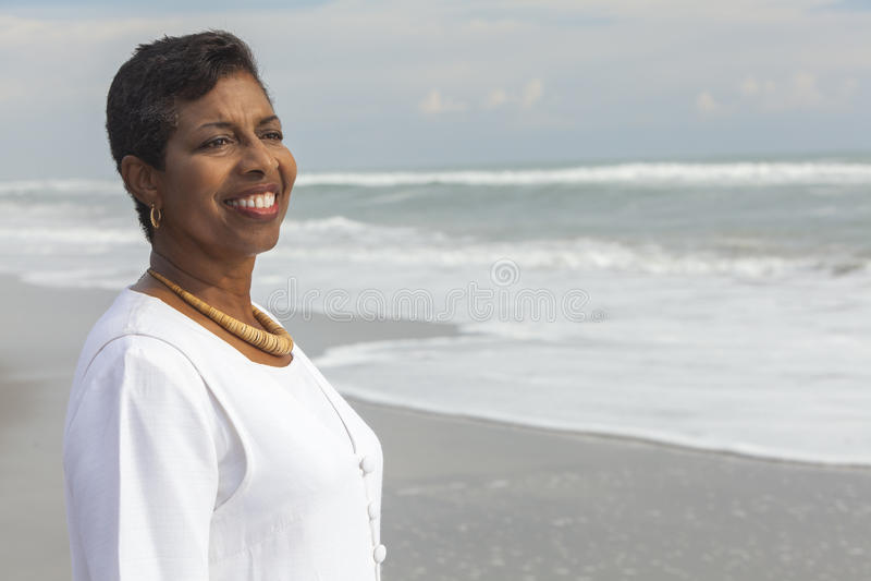 Lycklig stolt hög afrikansk amerikankvinna på stranden royaltyfria bilder