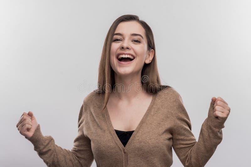 Lycklig stråla student som känner sig extremt tillfredsställd efter övergående examen arkivfoto