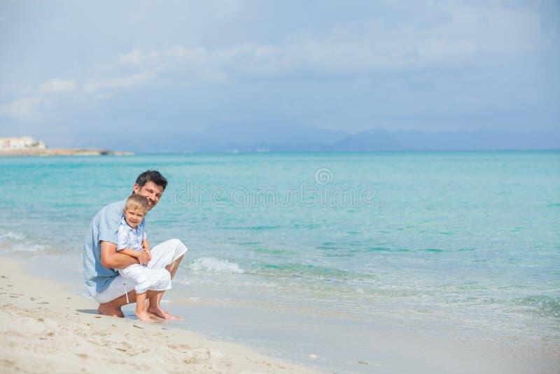 lycklig strandfader hans leka son royaltyfria foton