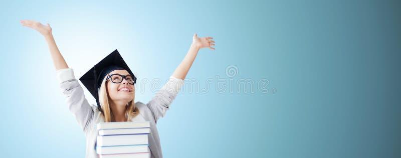 Lycklig student i mortelbrädelock med böcker royaltyfri bild
