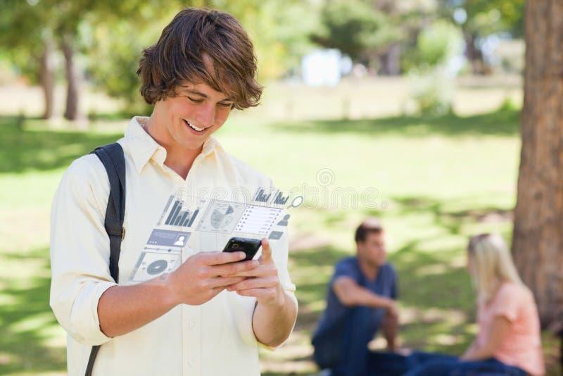 Lycklig student som arbetar på hans digitala smartphone arkivfoto