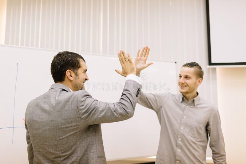 Lycklig student som ger ett högt-fem till en professor på en suddig bakgrund bollar dimensionella tre arkivbilder