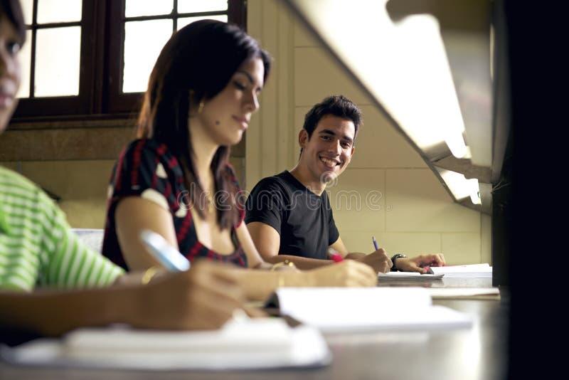 Lycklig student som studerar och skriver arkivbild