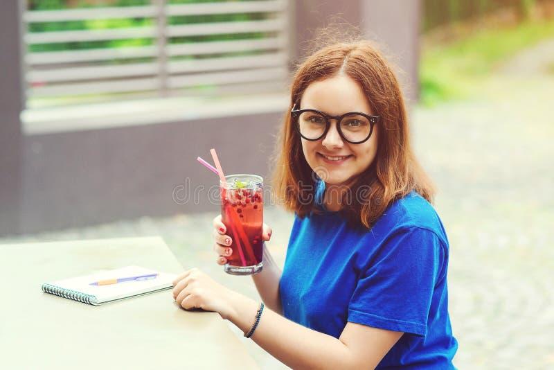 Lycklig studentflicka i exponeringsglas som utomhus dricker ny lemonad på kafét Hipsterflicka som rymmer sommarcoctailen Uppfrisk arkivfoton
