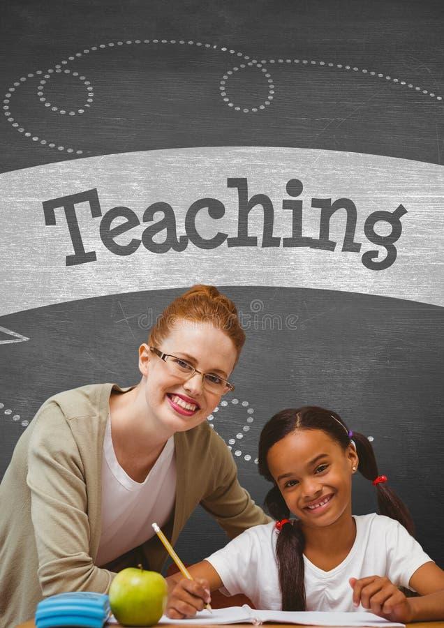 Lycklig studentflicka och lärare på tabellen mot den gråa svart tavla med undervisningtext och utbildning och royaltyfria bilder