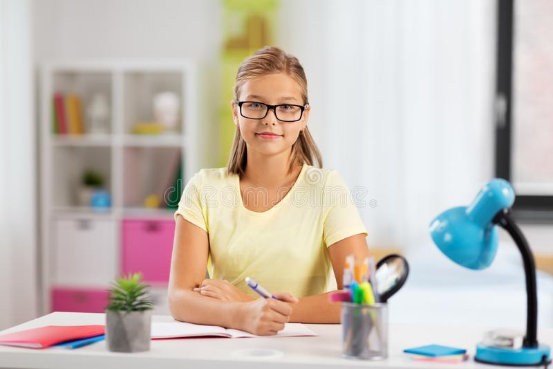 Lycklig studentflicka som hemma gör läxa arkivfoto